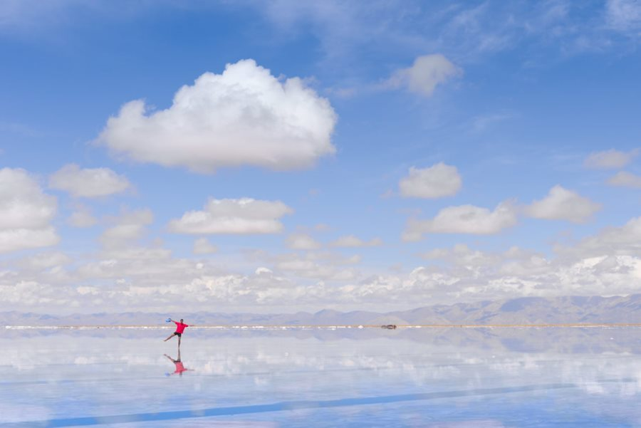 Water over the salt flats and man standing on it