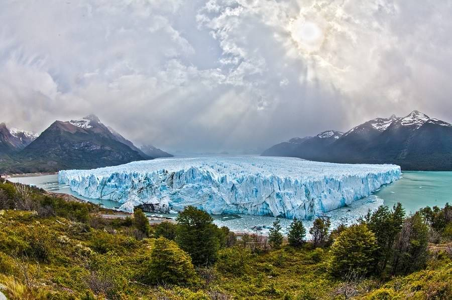Panoramic view of the Glaciar Perito Moreno, white blue ice, turquoise colored lake, dark gray stormy sky, forest and mountains